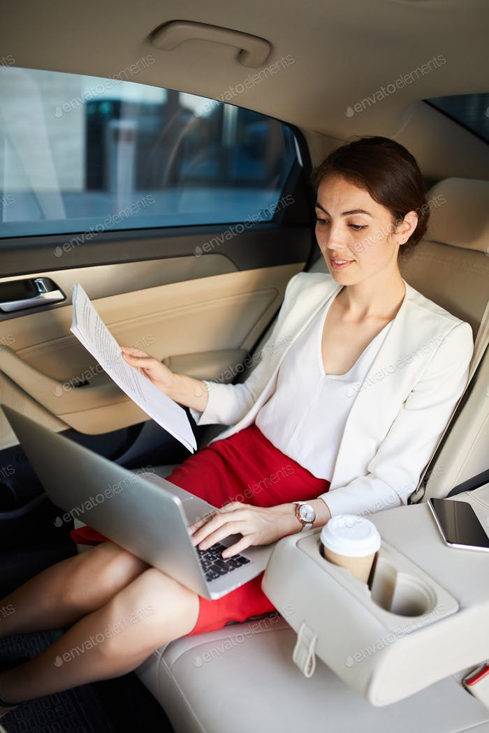 Businesswoman Working in Taxi