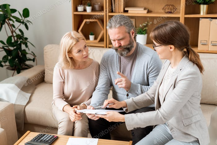 Young elegant female agent consulting mature man and woman in office
