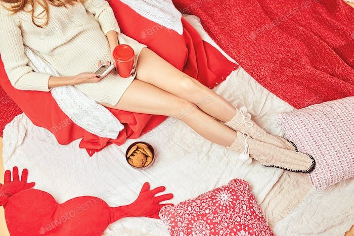 Girl dressed knitted dress and knitted socks lies on red-white blankets and pillows with a red cup