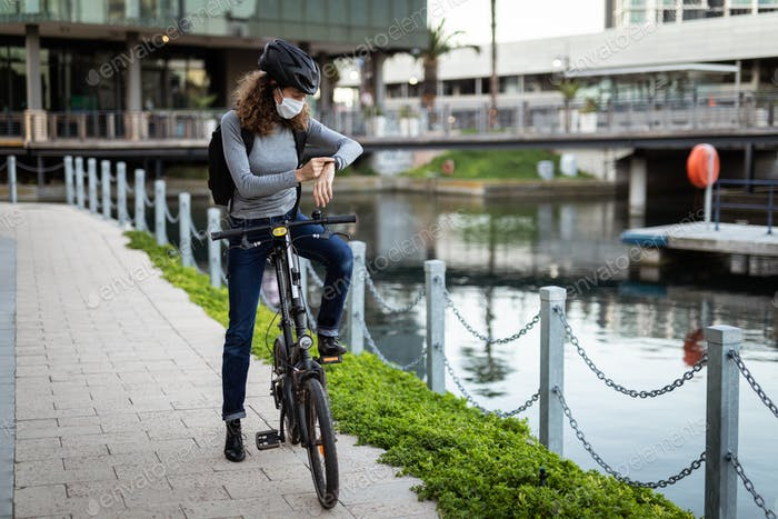 Caucasian woman wearing a protective mask and a cycling helmet in the streets, checking her smar
