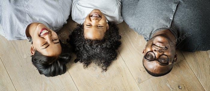 Black family lying on wooden floor design space