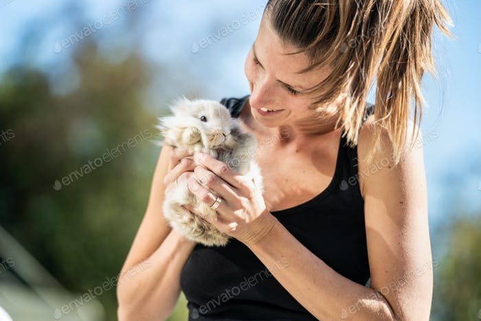 Young smiling woman holding furry baby rabbit