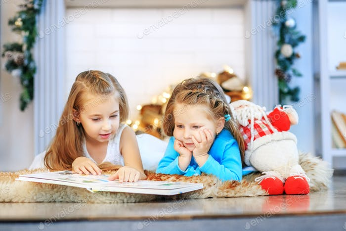 Two kids read a book. Two sisters. Concept New Year, Merry Chris