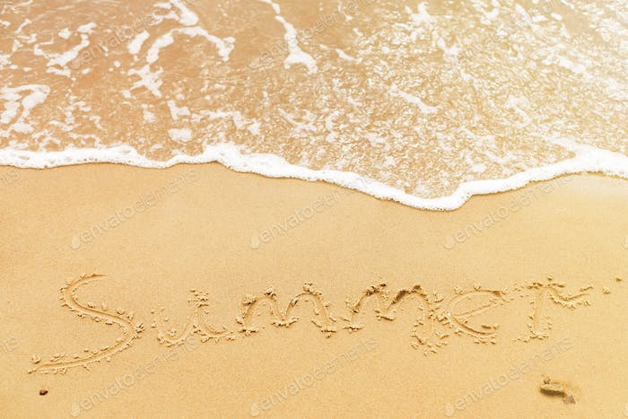 Summer text written on sandy beach and sea waves