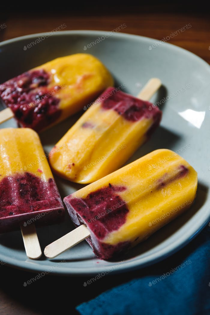 Fruit homemade popsicles made are from fresh mango, blackcurrant and coconut milk