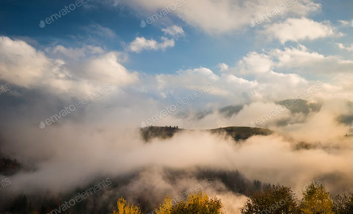 Foggy mountains under sky with clouds