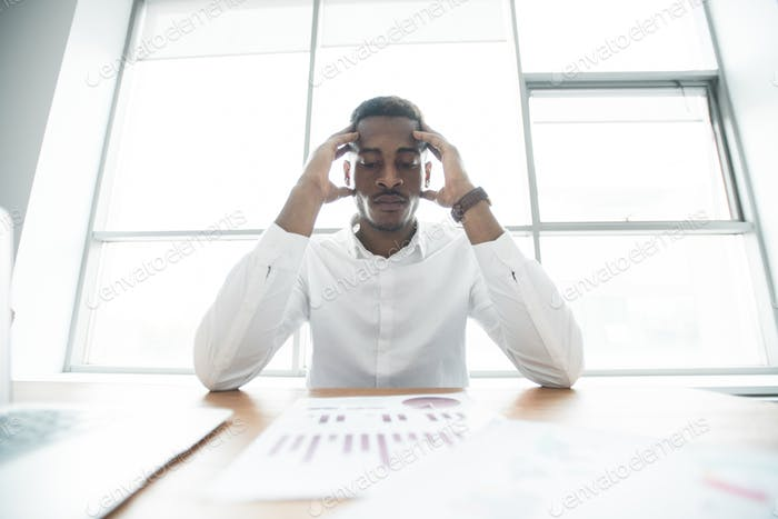 Puzzled African businessman analyzing graphs