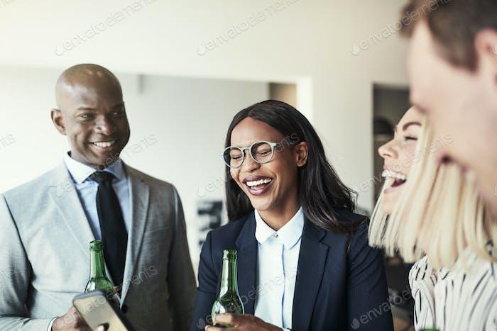 Разнообразная группа смеяных бизнесменов, употребляющих напитки в офисе