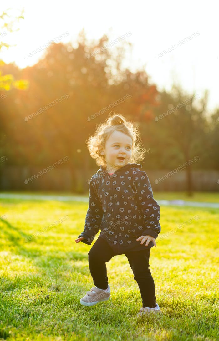 Little baby girl plays in the park in backlight.
