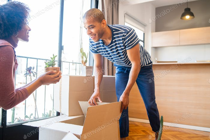 Couple packing cardboard box to move in new apartment.