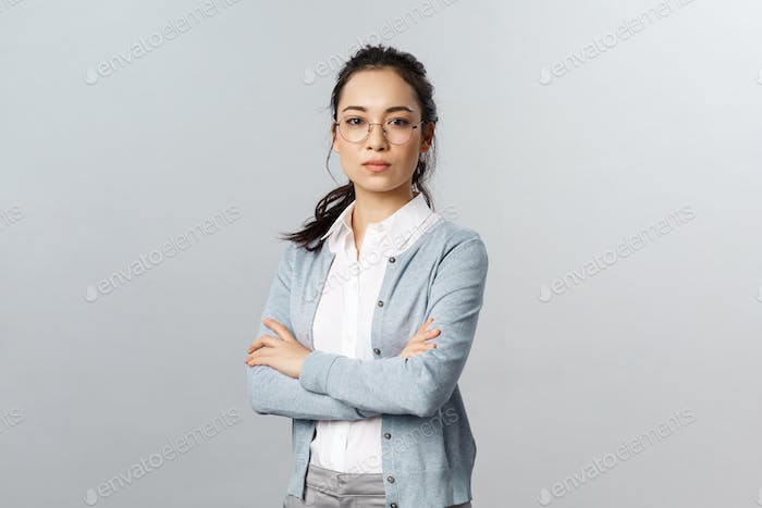 Serious-looking determined attractive asian woman, tutor or teacher starting online lesson with