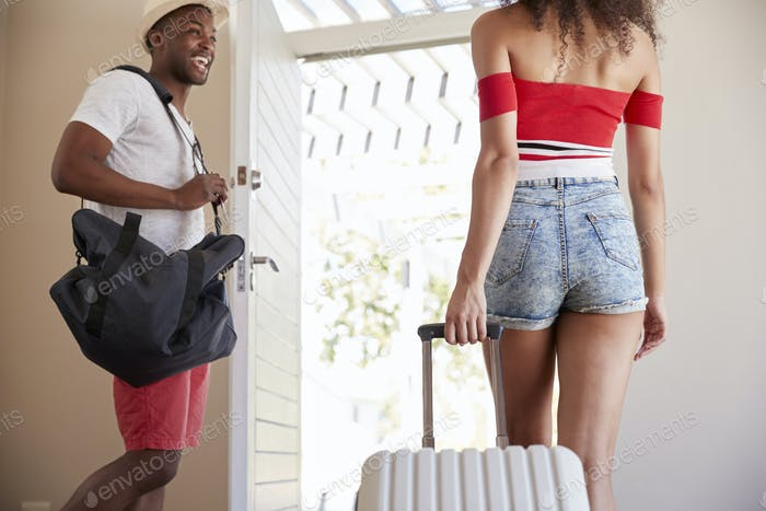 Couple With Luggage Leaving Home For Vacation