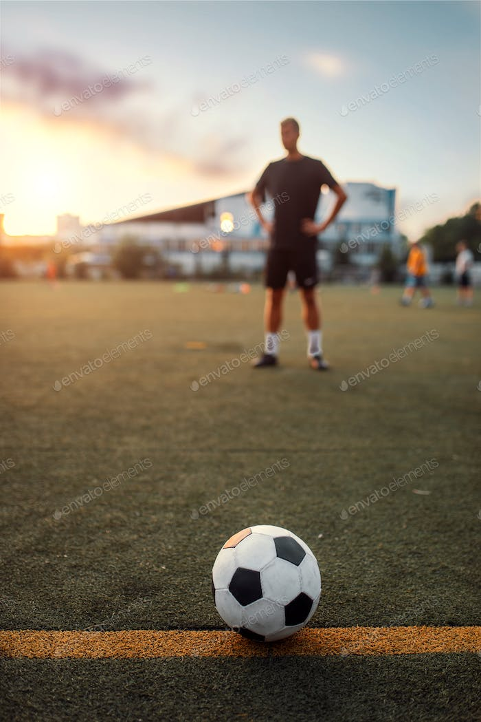 Soccer ball on line, player on background
