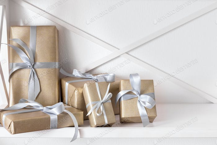 Elegant presents, gift boxes on white shelves background, closeup