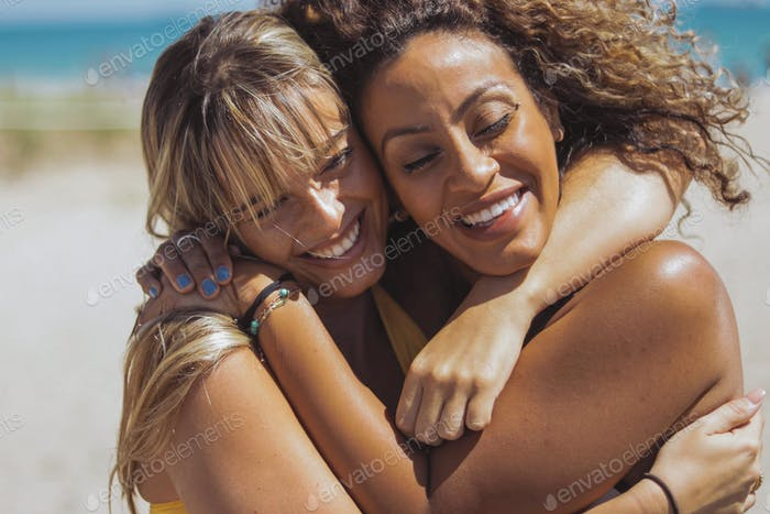 Embracing happy diverse women on beach