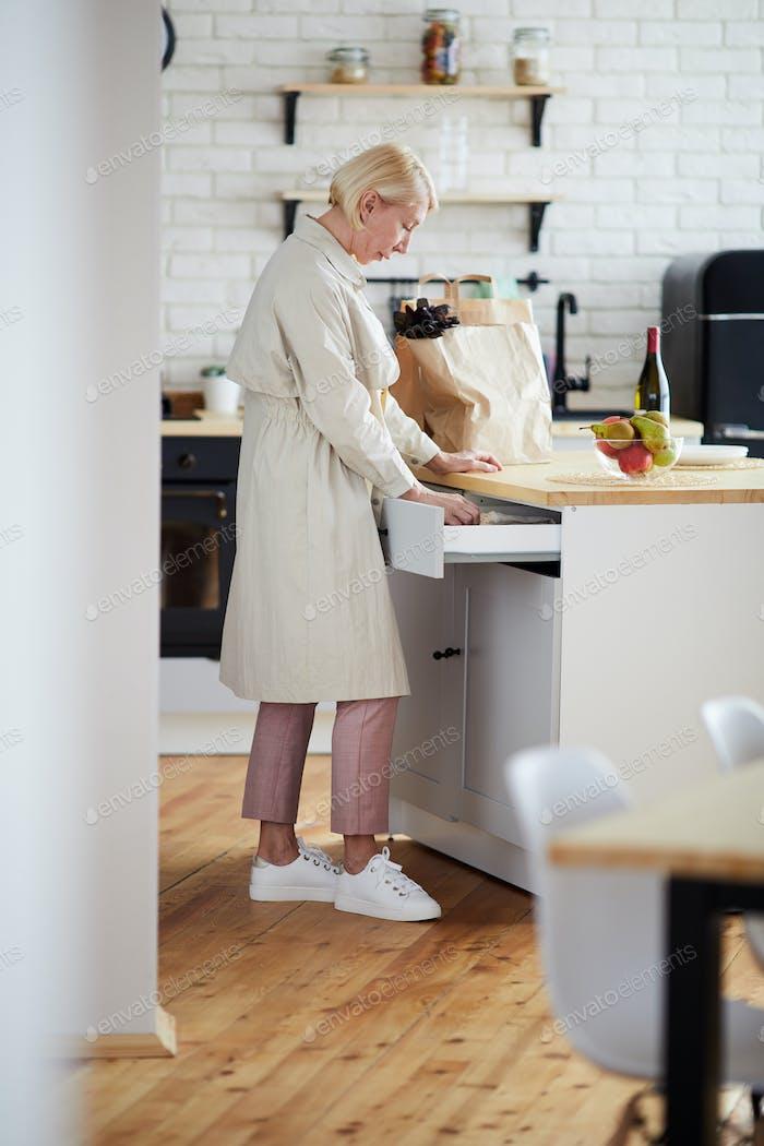 Woman finding utensil in kitchen drawer