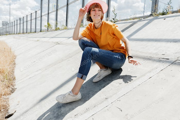 Smiling girl in yellow t-shirt, jeans and pink visor is sitting on a concrete slab next to glass