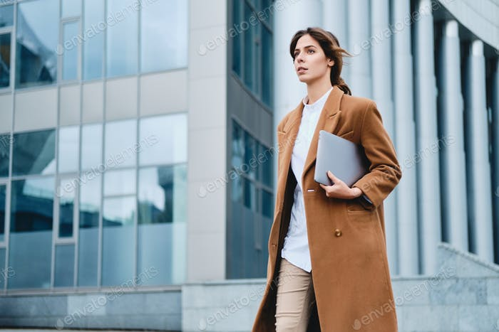 Young attractive businesswoman in coat with laptop confidently walking through city street