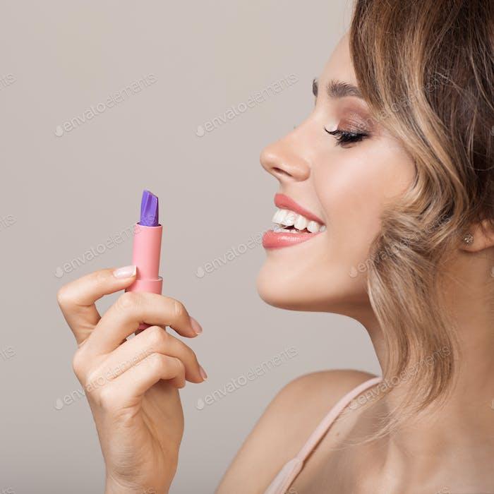 Attraktive lächelnde Frau hält Lippenstift in der Hand.