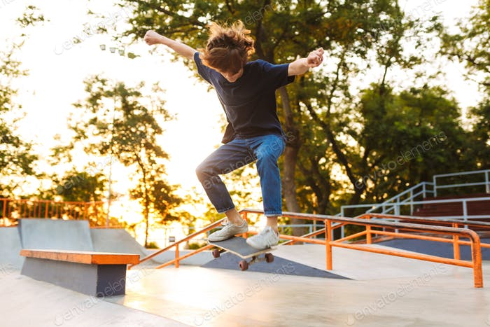 Young cool skater in black T-shirt and jeans practicing jumping