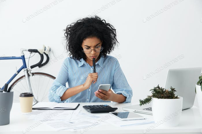 Frustrated young female entrepreneur in formal shirt and eyewear having a problem while working on f