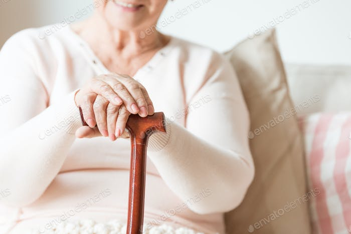 Close-up of the hands of a happy, elderly woman resting on a woo