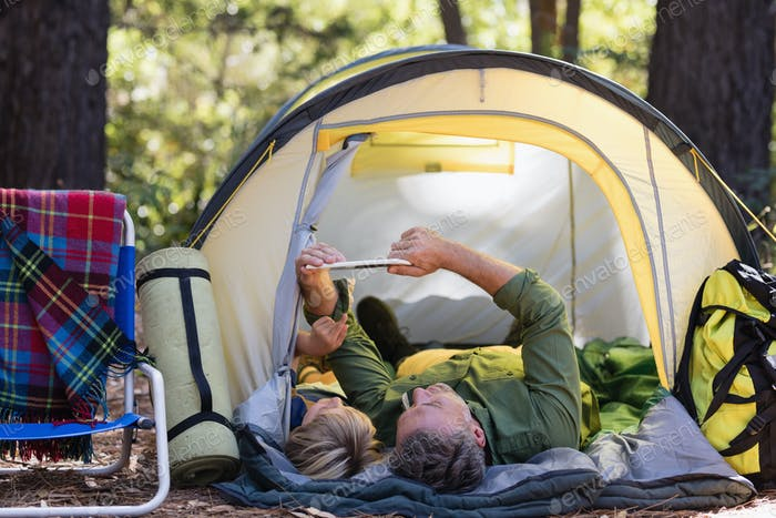 Father and son using digital tablet while relaxing at campsite