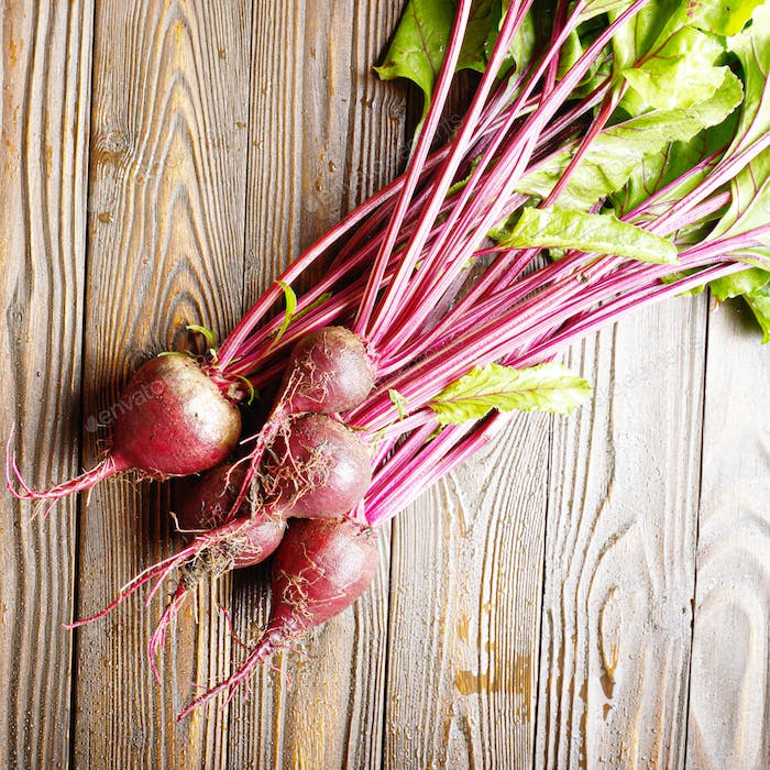Top view at Fresh organic beetroots on kitchen wooden rustic tab