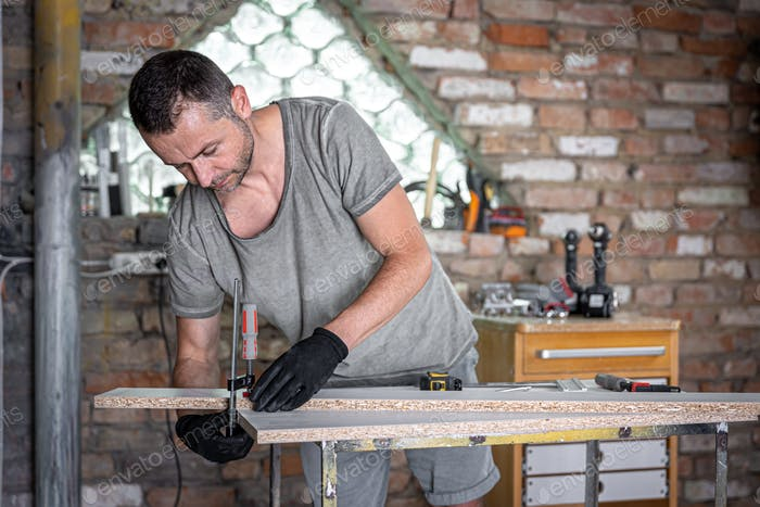Carpenter using f clamp to set up wood in wood working.