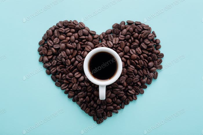 Heart Shape Made of Coffee Beans and Cup of Black Coffee on Blue Flat Lay.