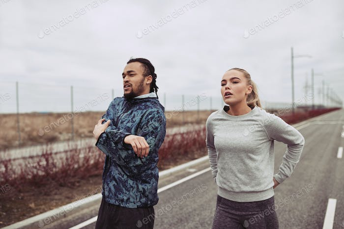 Diverse young couple warming up together before a road run