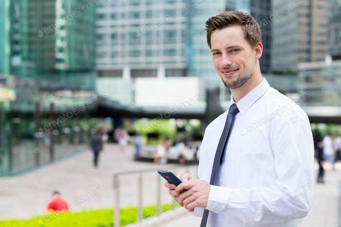 Geschäftsmann hält mit Handy im Freien