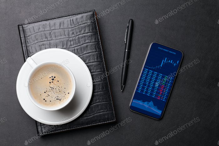 Office desk with coffee, notepad, phone and pen