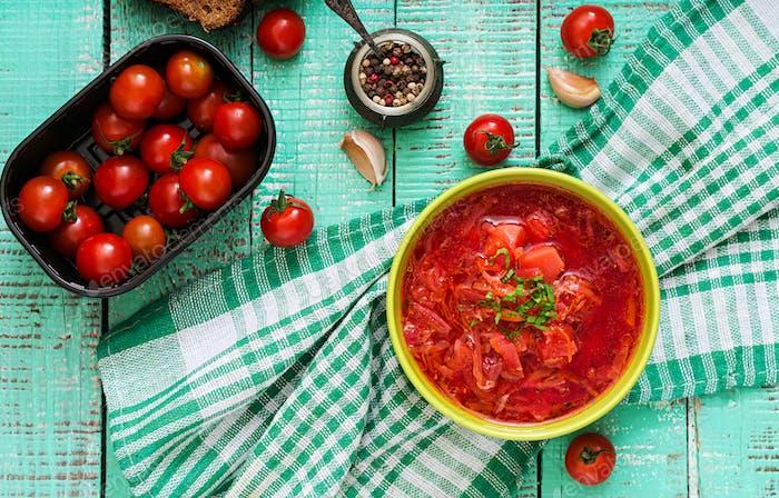 Traditional Ukrainian Russian vegetable borscht soup on green bowl. Flat lay. Top view