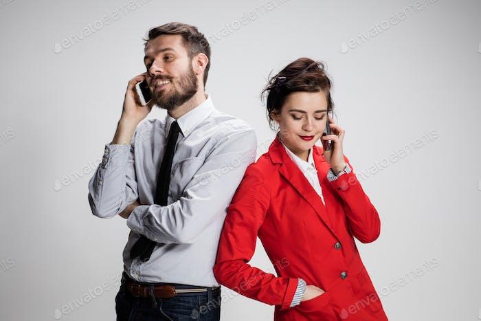 Geschäftskonzept. Die beiden jungen Kollegen halten Mobiltelefone auf grauem Hintergrund