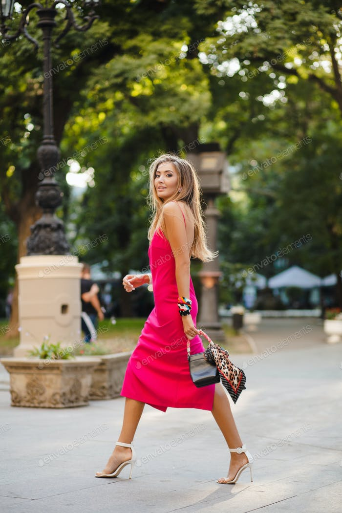elegant attractive woman wearing pink sexy summer dress walking in street
