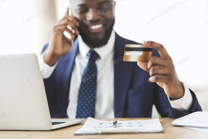 Happy young man holding credit card, talking on phone