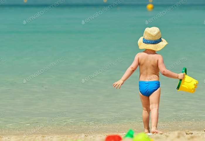 Two year old toddler playing on beach