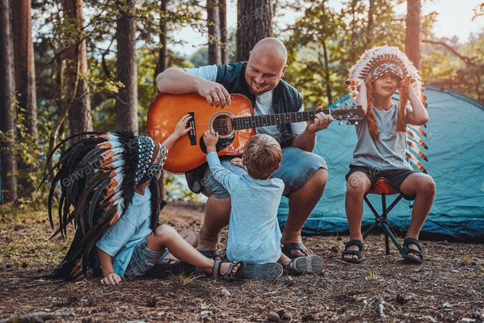 American father teaching his boys to play guitar