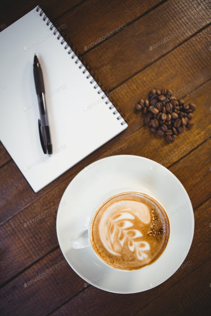 Cup of cappuccino with coffee art and notepad on wooden table