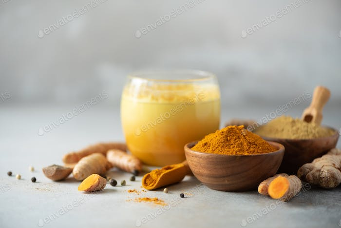 Healthy vegan turmeric latte or golden milk, turmeric root, ginger powder, black pepper over grey
