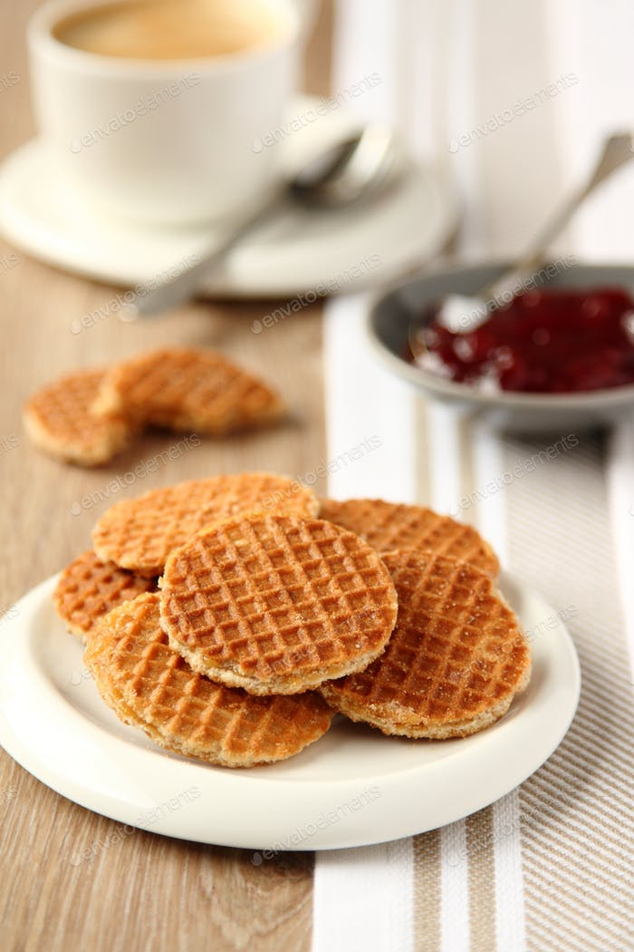 Mini stroopwafels (syrupwaffles) with cup of coffee and jam