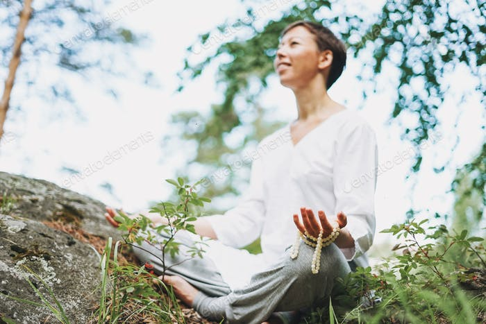 Young smiling woman practice yoga outdoors