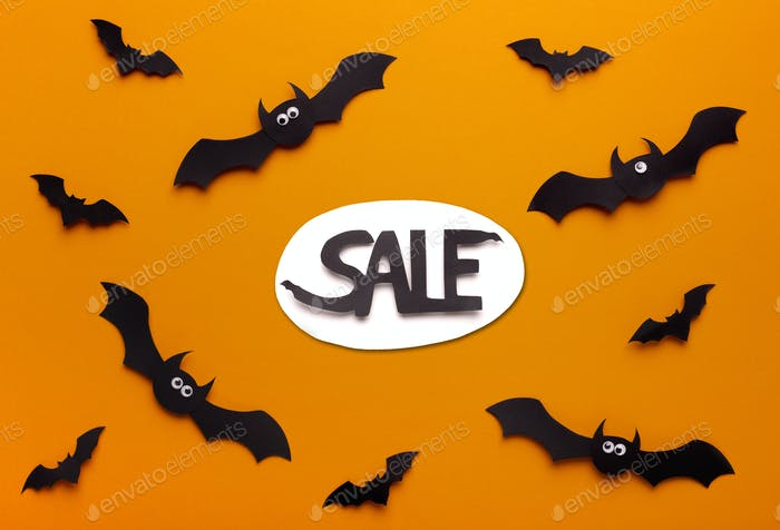 Flying paper bats on orange background with promo text