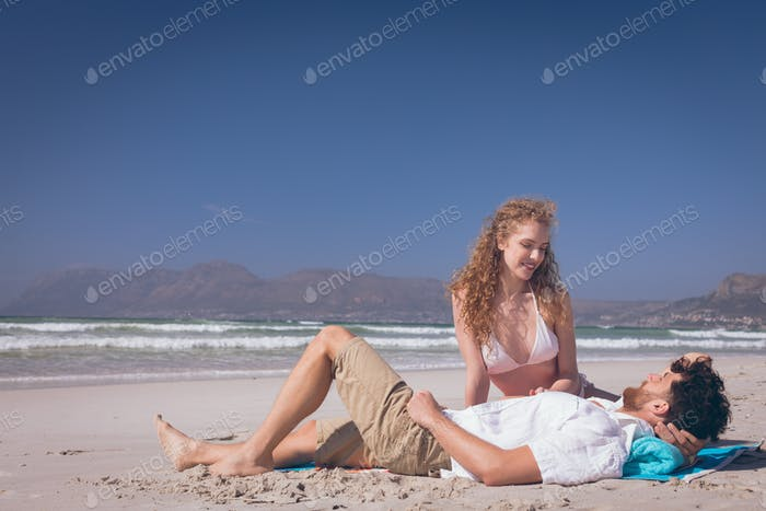Romantic couple interacting with each other at beach on a sunny day
