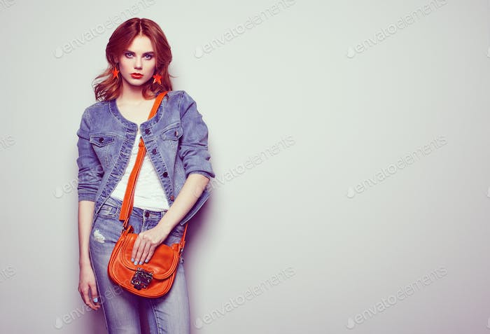 Fashion portrait of beautiful young woman with handbag