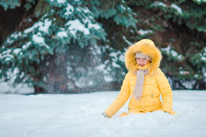 Happy little adorable girl in snow outdoors