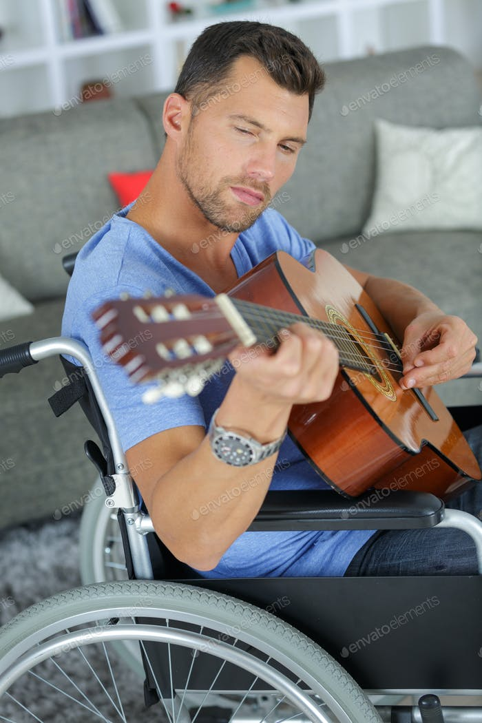 man on the wheelchair playing the guitar