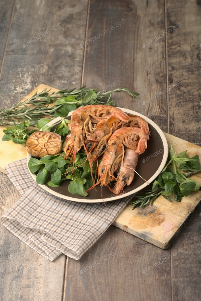 Boiled shrimp with fresh tomatoes and leaves of salad on ceramic plate. Top view.