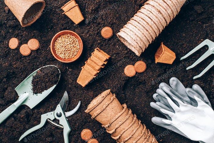 Gardening tools over soil background. Gardening tools, seeds, pruner, rake, shovel, biodegradable
